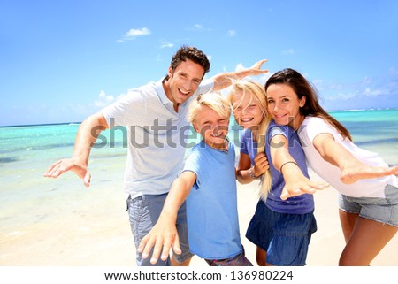 Happy couple with kids at the beach - stock photo