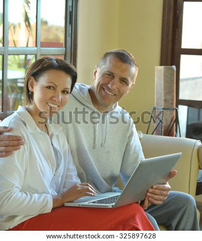 Happy couple with laptop on a sofa