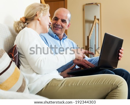 Happy couple with notebook at table at home