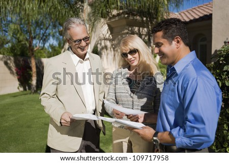 Happy couple with real estate agent discussing paperwork - stock photo