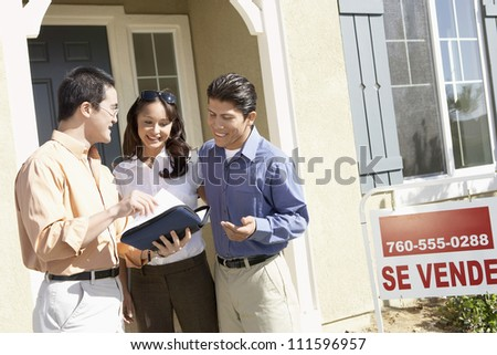 Happy couple with real estate agent in front of new house