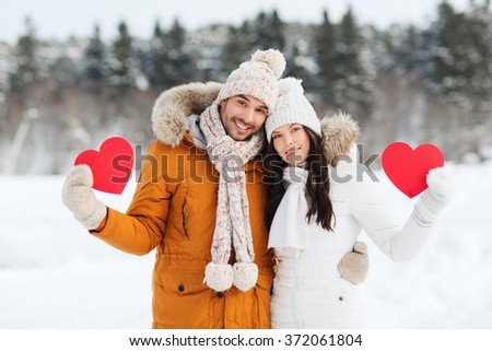 happy couple with red hearts over winter landscape - stock photo