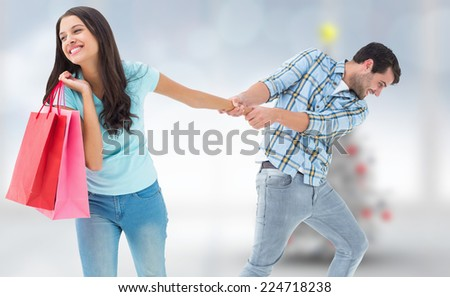Happy couple with shopping bag against blurry christmas tree in room - stock photo