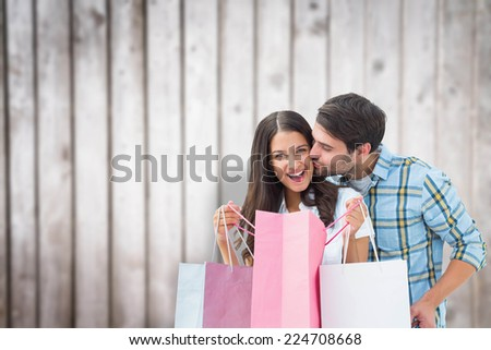 Happy couple with shopping bags against blurred wooden planks - stock photo