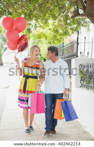 Happy couple with shopping bags and balloons walking on sidewalk in city - stock photo