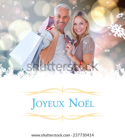 happy couple with shopping bags and credit card against Christmas greeting card - stock photo