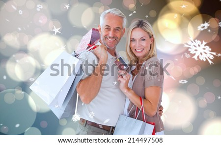 Happy couple with shopping bags and credit card against light glowing dots design pattern - stock photo