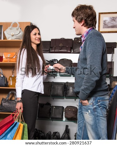 Happy couple with shopping bags at the mall. Man giving credit card to woman