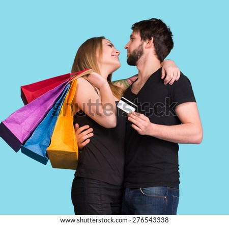 Happy couple with shopping bags on a blue background. Man holding credit card