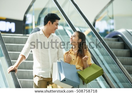 Happy couple with shopping bags on escalator