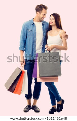 Happy couple with shopping bags, standing close and looking to each other with smile. Caucasian models in love, holiday sales, shop, retail, consumer concept.