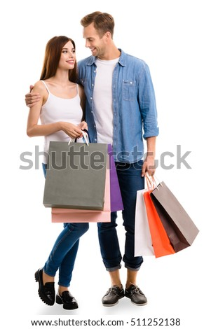 Happy couple with shopping bags, standing close and looking to each other with smile. Caucasian models in love, holiday sales, shop, retail, consumer concept, isolated on white background.