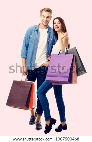 Happy couple with shopping bags, standing close to each other with smile. Caucasian models in love, holiday sales, shop, retail, consumer concept.