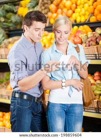 Happy couple with shopping list against the stacks of fruits decides what to buy