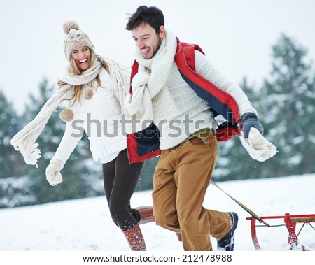 Happy couple with sled running through snow in winter - stock photo