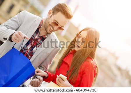 Happy couple with smart phone and shopping bags in the city - stock photo