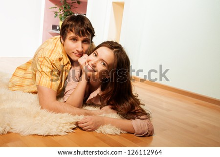 Happy couple with smling wife laying on the floor with husband in living room - stock photo