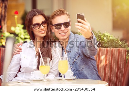 happy couple with sunglasses taking selfie in a cafe  - stock photo