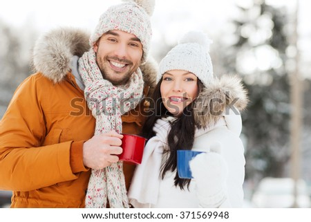 happy couple with tea cups over winter landscape - stock photo