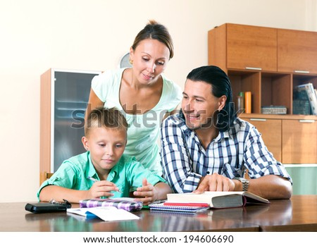 Happy couple with teenager schoolboy doing homework together in home interior