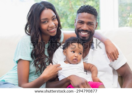 Happy couple with their baby girl on couch at home in the living room