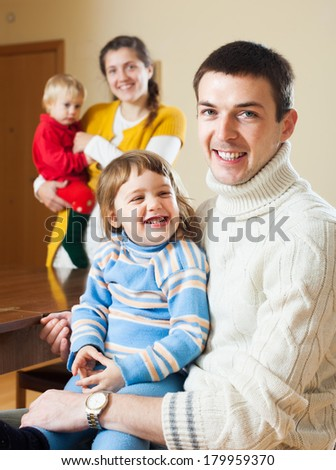 Happy couple with two children at home   - stock photo