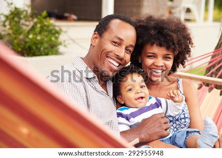 Happy couple�¿with young child sitting in a hammock - stock photo