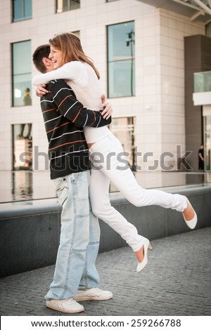 Happy couple - young man welcomes her girlfriend on street - full lenght composition - stock photo