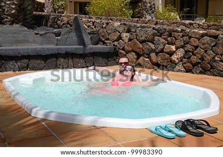 Happy couples relaxing in tropical jacuzzi - stock photo