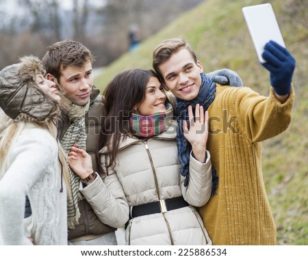 Happy couples taking self portrait through cell phone in park