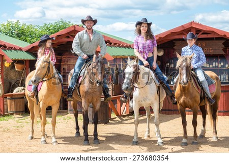 happy cowboy family of four on horsebacks waving their hands - stock photo