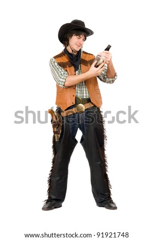 Happy cowboy with a bottle of whiskey in hand - stock photo