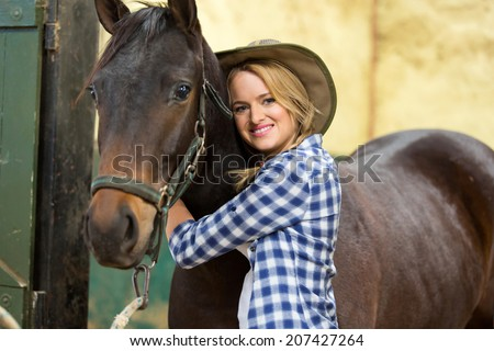 happy cowgirl hugging her horse inside stable