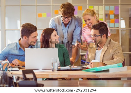 Happy creative business team using laptop in meeting at office