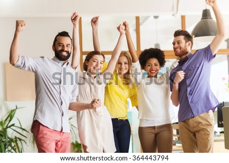 happy creative team celebrating victory in office - stock photo