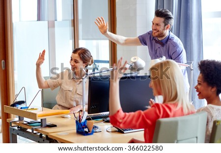 happy creative team waving hands in office - stock photo