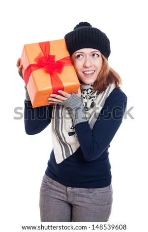 Happy curious woman in winter clothes holding present, isolated on white background. - stock photo