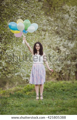Happy curly brunette with balloons near blooming tree in spring