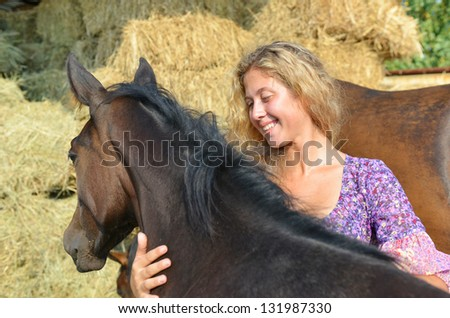 Happy Curly haired blonde girl and her horses near haystack