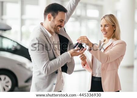 Happy customer just bought a car at car dealership - stock photo