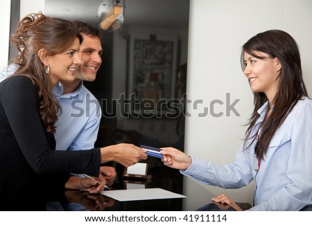 Happy customers paying at the hotel with a credit card - stock photo