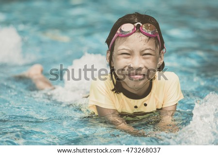 Happy cute asian child playing in swimming pool. Summer vacation concept.vintage style image process
