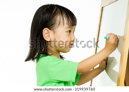 Happy cute Asian Chinese toddler girl drawing or writting with marker pen on a blank whiteboard at home, preschool, daycare or kindergarten in plain white isolated background.