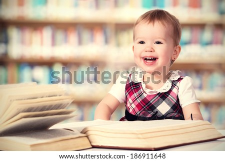 Happy cute baby girl reading a book in a library - stock photo