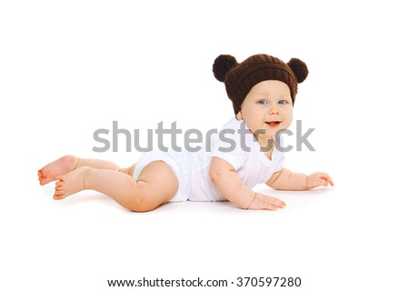 Happy cute baby in knitted brown hat with ears bears crawls on white background - stock photo