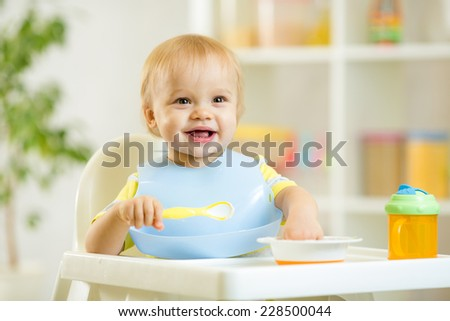 happy cute baby kid boy eating food itself with spoon - stock photo