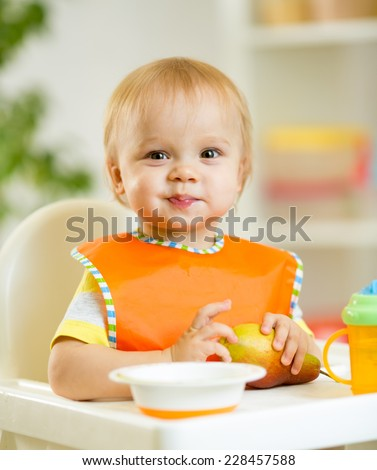 happy cute baby kid toddler eating itself with spoon - stock photo