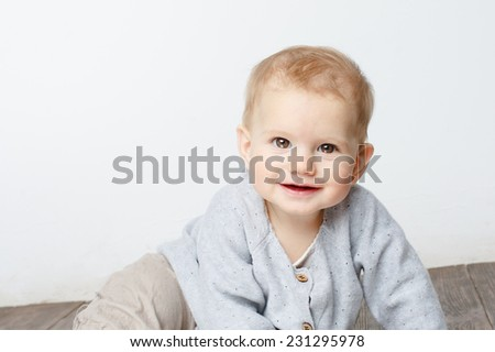 happy cute baby looking into the camera. The baby sitting  over white wall - stock photo