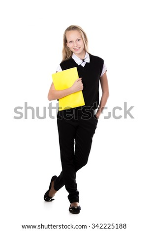 Happy cute beautiful blond schoolgirl wearing black formal outfit with bow tie, holding yellow folder, posing, friendly smiling, isolated studio shot, white background, full length - stock photo