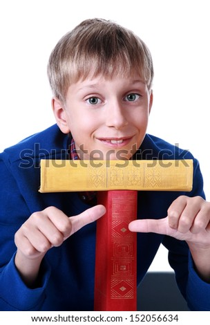 Happy cute blond boy in a blue sweater sitting with two colorful hardcover books (isolated on white background) showing thumbs up gesture - stock photo